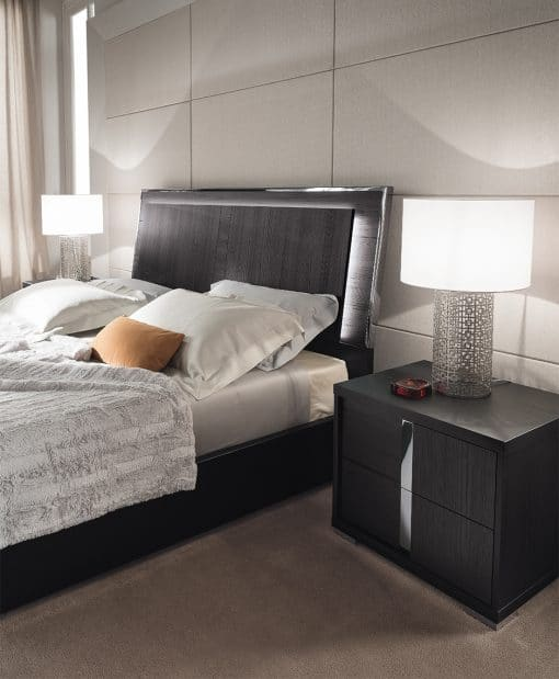 Image depicts a bedroom with modern furniture, including a bed and night stands.