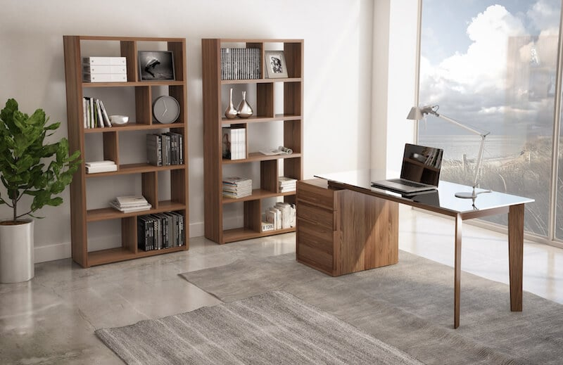 Image depicts a home office furnished with modern office furniture, including a desk and a bookcase.